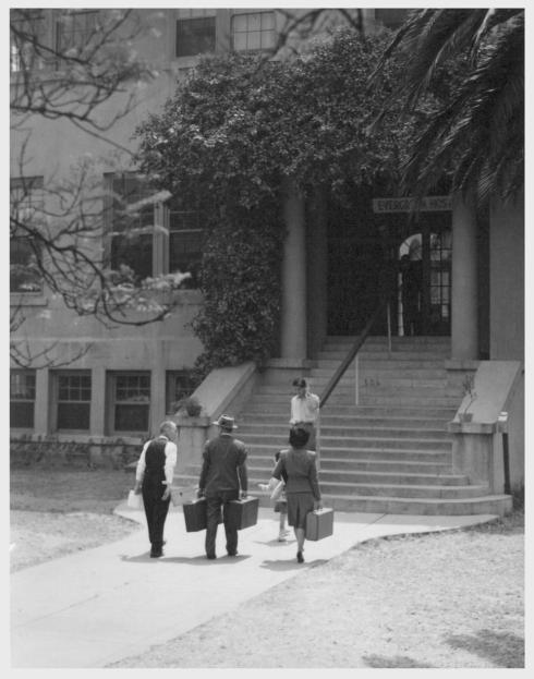 James Shimokawa, his wife Jennie and their little son Gary, age 3, shown living at the Evergreen Hostel, Los Angeles. They left Manzanar in 1943 to go to Idaho, then moved to Denver, and on June 1, stepped out of a taxi in front of the hostel, where they were welcomed by Rev. S. Kowta. The Evergreen Hostel is a quiet part of Los Angeles on the east side, and occupies the building used before the war as a Presbyterian Church School for Japanese children. Rev. S. Kowta, Presbyterian Minister, and Esther Rhoades manage the hostel, under the auspices of the Presbyterian Church and the American Friends. Eighty to ninety people--men, women, and children--are accommodated at one time at the hostel. Room and meals are only $1 a day to start, and $1.50 after the first week. -- Photographer: Mace, Charles E. -- Los Angeles, California. 6/1/45