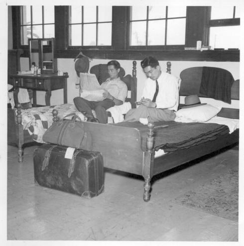 Henry Suenaga (reading newspaper) from Manzanar, and Ben Nishiyama from Poston, relaxing in a section of one of the men's dormitories at Evergreen Hostel, Los Angeles. Both are looking for homes. Ben first went to Minneapolis from Poston, and Henry to Mississippi from Manzanar. They enjoy the comfortable dormitory and good meals at low cost at the Evergreen Hostel. Conditions in Los Angeles are good, and there are jobs though not as many as the east--but finding a home is a tough proposition, the young men say. That goes for anyone, any race. -- Photographer: Mace, Charles E. -- Los Angeles, California. 6/1/45