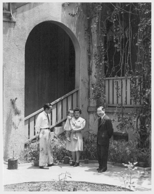 Mr. George Yanase, his wife Ann, their little girl Robbie Jeane (age 19 months), and Rev. S. Kowta, all from Poston, in the patio of Evergreen Hostel, Los Angeles. Mr. and Mrs. George Yanase left Poston a year and a half ago to move to Pagosa Springs, Colorado, where he does garage work. Before the war, they lived at Anaheim, California. They plan to return to Pagosa Springs, and their three other children at Poston will join them. Meantime at Evergreen Hostel, Mr. and Mrs. Yanase and Robbie Jeane are comfortably housed and fed. Rev. Kowta is one of the two managers of the Evergreen Hostel. -- Photographer: Mace, Charles E. -- Los Angeles, California. 6/1/45