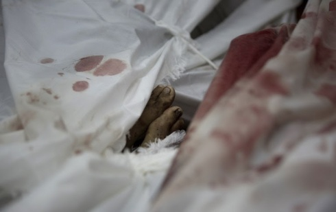 The body of Ali al-Shibari, a 10-year-old Palestinian child who was killed after a UN school in the northern Beit Hanun district of the Gaza Strip was hit by an Israeli shell, lies wrapped in shrouds at the morgue of the Kamal Adwan hospital in Beit Lahiya on July 24, 2014: photo by Mahmud Hams / AFP, 24 July 201
